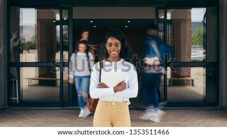 Portrait of girl student standing at university campus with other students walking in background. Young woman standing in college with students walking at the back. #1353511466