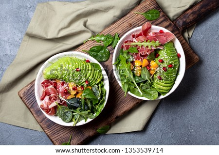 Low carbs bowl. Fresh salad with green spinach, rucola, avocado an ham serrano in white bowl, gray background, top view. #1353539714