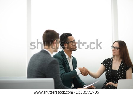 welcoming handshake of a businessman and businesswoman . #1353591905