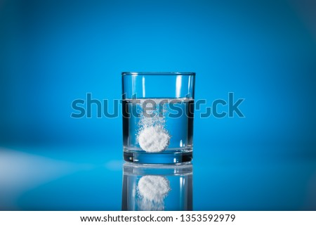 Effervescent tablet dissolving in a glass of water at blue background with copy space