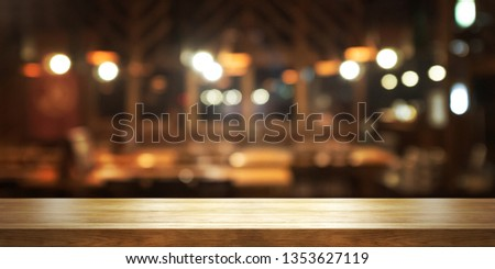 Empty wooden table top with blur coffee shop or restaurant interior background, Panoramic banner. Abstract background can be used for display or montage your products.  #1353627119