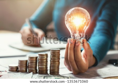 business woman hand holding lightbulb with coins stack on desk. concept saving energy and money #1353671060