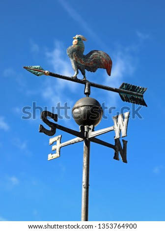old vintage weathercock in iron on blue sky background #1353764900