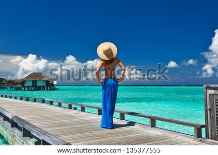 Woman on a tropical beach jetty at Maldives #135377555