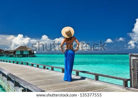 Woman on a tropical beach jetty at Maldives #135377555