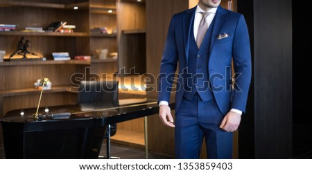 Man model in expensive custom tailored suit standing in his office and posing #1353859403
