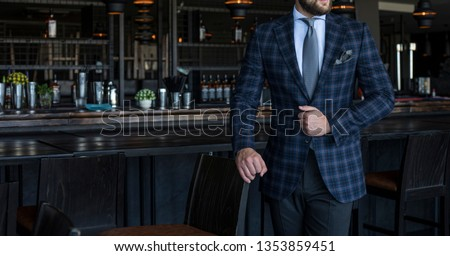 Man in expensive custom tailored suit with checked pattern standing and posing inside bar #1353859451