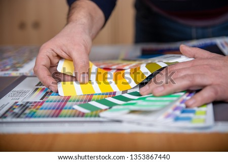Worker in a printing and press center uses a color palette to select the correct shade of color from CMYK printed sheet.