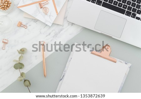 Office desk table with laptop, clipboard, rose gold pen, clips and supplies, pretty eucalyptus branches on marble gray background. Top view with copy space Royalty-Free Stock Photo #1353872639