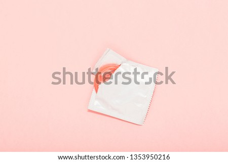 Pink opened condom and condom in pack on a pink background. A condom use to reduce the probability of pregnancy or sexually transmitted disease (STD). Safe sex and reproductive health concept. #1353950216