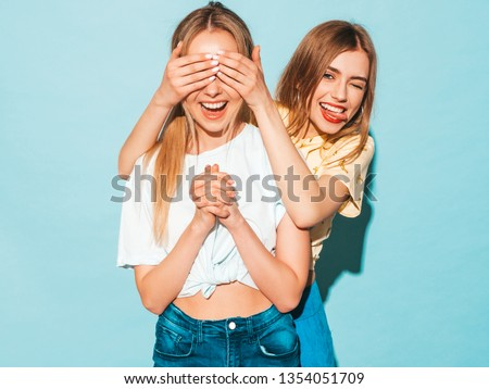 Girl surprising her female best friend. Model covering her eyes and hugging  from behind. Two surprised girls. Women having fun and showing face emotions