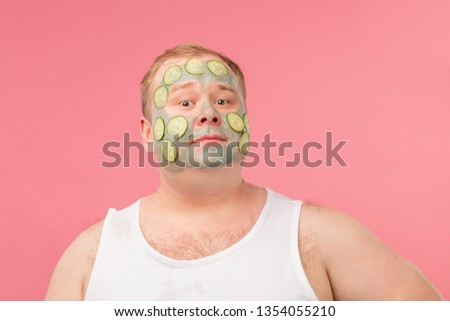 Happy funny tubby man with facial clay mask for skin care having fun with cucumber slices isolated over pink background #1354055210