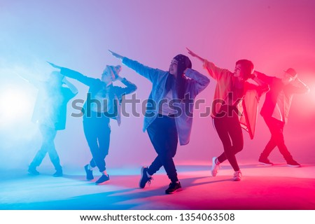 Young modern dancing group of six adult young people practice dancing on colorful background. Fashionably dressed youngsters moving over blurred disco club color lights #1354063508