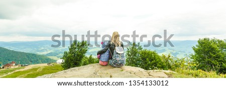 Mother and daughter admire beauty in the mountains #1354133012
