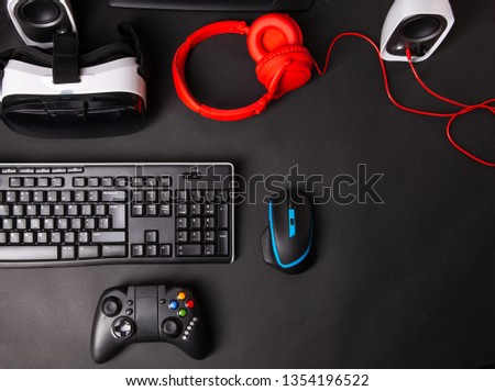Top view a gaming gear, mouse, keyboard, joystick, headset, VR Headset on black table background. #1354196522