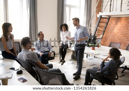 Confident male leader, coach talking with multiracial group of office workers, having good conversation with subordinate, brainstorming, discussing business strategy, ideas, team building activity #1354261826