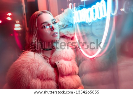 Teen hipster girl in stylish glasses and fur posing near neon sign on street, female teenager fashion model woman with beautiful face looking at camera in city night light glow, back to 80s, portrait #1354265855