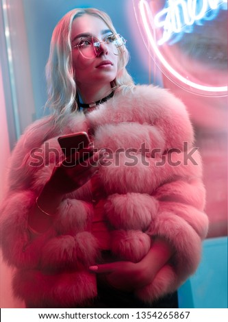 Teen hipster girl in fur glasses use cellphone mobile event dating app looking away stand near neon street sign, teenager young woman holding phone text messages in city night light glow, back to 80s #1354265867
