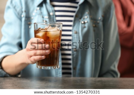 Woman holding glass of cola with ice at table, closeup #1354270331