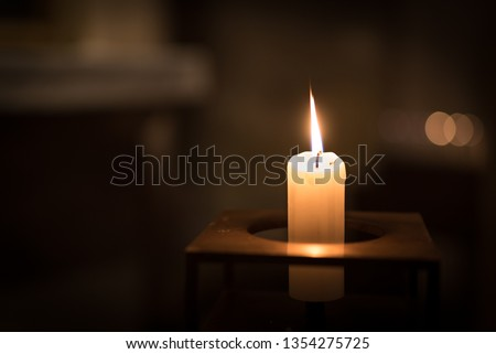 A single candle burning inside a church. The candle is made of pale wax and is in a square metal candle holder. The candle flame is sharp, and the background has soft bokeh. #1354275725
