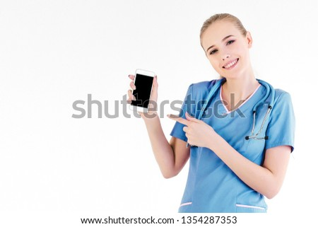 Girl nurse blond gray background day beautiful in hands phone shows hand finger smiling call be in touch hospital. Online communication with doctor. Close up copy space left. #1354287353