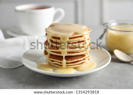 Plate with pancakes and condensed milk served on table. Dairy product Royalty-Free Stock Photo #1354293818