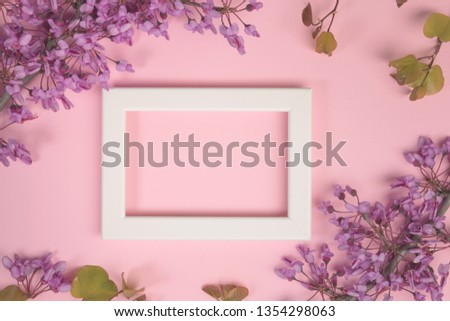 Flowers composition. Purple flowers, leaves and photo frame on pastel pink background. Flat lay, top view, copy space