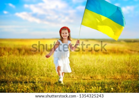 Ukraine s blue-yellow flag flying in wind in hands of little Ukrainian girl on Day of ndependence of Ukraine. Symbols of Ukraine in hands of a smiling child against blue sky and yellow grass. #1354325243