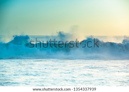 Abstract sunset seascape background. Crashing Pacific Ocean sea waves in beautiful soft yellow sunsetting light on California beach, USA. Pale pastel teal to Tiffany blue greens of water and skies #1354337939