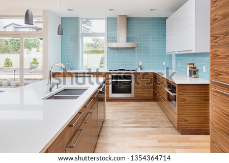 Beautiful Kitchen in Contemporary Luxury Home with Waterfall Island, Counter to Ceiling Backsplash Tile, and Elegant Hardwoods #1354364714