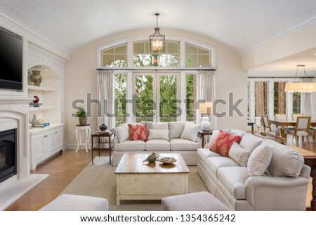 Beautiful living room in new luxury home with French Doors, Fireplace, Built-Ins, and View of Dining Room #1354365242