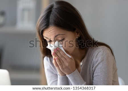 Sick young woman sitting indoors holding tissue handkerchief blowing running nose feels unwell unhealthy, girl having symptoms of chronic sinusitis disease, seasonal allergy or cold fever flu concept #1354368317