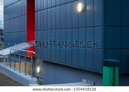 Descent to the basement. Stair down. New building. Beautiful stylish tiled red-blue facade. Lamp and green trashcan. #1354418126