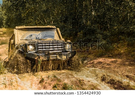 Jeep crashed into a puddle and picked up a spray of dirt. Off road sport truck between mountains landscape. Track on mud. 4x4 Off-road suv car. Offroad car. Safari. Best Off Road Vehicles #1354424930