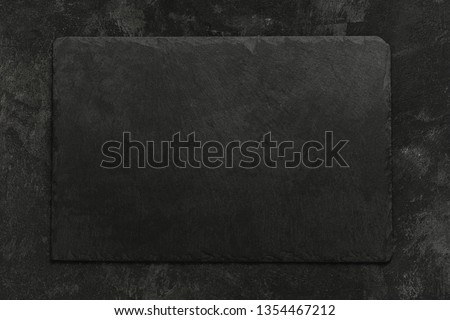 Black on black. Empty black granite stone rectangle board on black textured cement background, top view vith copy space for your text. #1354467212