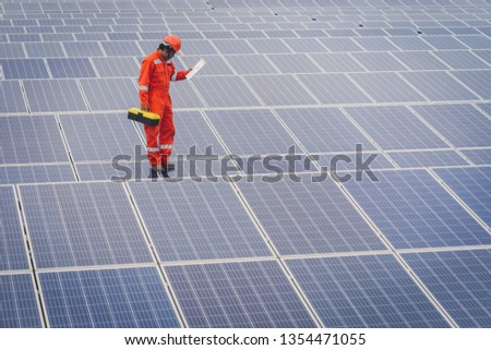 engineer in solar power plant working on installing solar panel ; operation of solar power plant by smart operator #1354471055