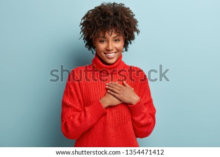 Photo of emotional dark skinned female touches heart with both palms, demonstrates thankful gesture, has good natured expression, expresses great sympathy, gratitude with honesty, feels love #1354471412