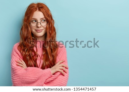 Pensive dreamy lovely young ginger female with pleasant appearance, imagines dreams come true, keeps hands crossed, dressed in oversized jumper, wears optical glasses, isolated over blue wall. #1354471457