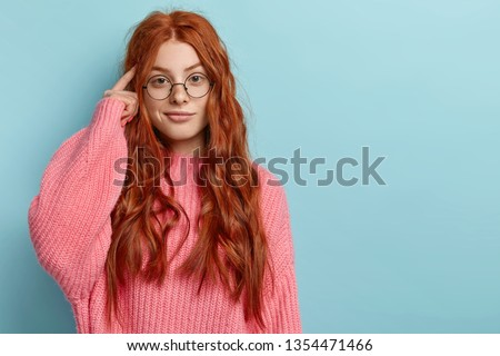 Photo of attractive ginger pupil with long wavy hair, tries to memorize something, keeps fore finger on temple, reminds information for exam, wears spectacles and jumper, stands over blue wall #1354471466