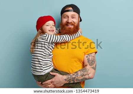 Isolated shot of happy father with ginger beard, yellow t shirt, carries small daughter, recieves hug with love, spend free time together in family circle, express positive emotions. Parents, children #1354473419