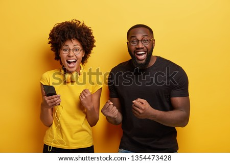 Overjoyed millennial dark skinned woman and man dance and clench fists from joy, listen music on cell phone, enjoy favourite playlist have fun together, use modern headphones, isolated over yellow #1354473428
