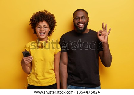 Waist up shot of joyful Afro American woman and man enjoy leisure time, listen music on cell phone. Dark skinned guy makes okay gesture, likes melody, stands near girlfriend. Lifestyle concept #1354476824