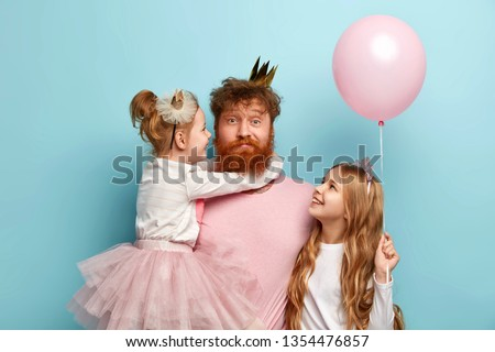 Busy father organizes holiday on International childrens day for two daughters, have home party, wear crowns and festive clothes. Little adorable girl holds air balloon, looks at dad and sister #1354476857