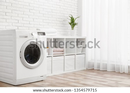 Modern washing machine near brick wall in laundry room interior, space for text #1354579715