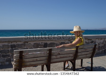 Young woman yellow t-shirt and hat resting on the seafront on a wooden bench. #1354647362