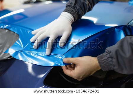 Car wrapping specialist putting vinyl foil or film on car. Selective focus.  Royalty-Free Stock Photo #1354672481