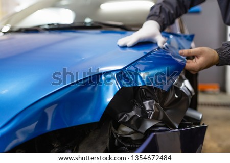 Car wrapping specialist putting vinyl foil or film on car. Selective focus.  Royalty-Free Stock Photo #1354672484