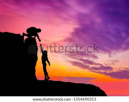 Silhouettes of two people climbing on mountain and helping. #1354690313