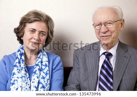 A high society senior couple (he's in his 80's, she's in her late 60's) sitting on a sofa looking at the camera. Medium close up. #135473996
