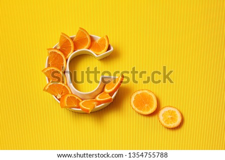 Vitamin C in food concept. Plate in shape of letter C with orange slices on bright yellow background. Ascorbic acid is important for immune system function. #1354755788